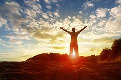 libération un homme lève les bras au lever du soleil